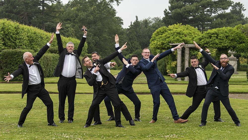 Group of groomsmen pointing to sky