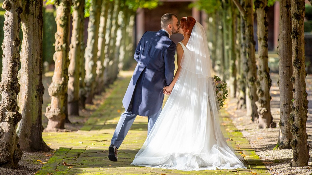 bride and groom kiss in arch of trees
