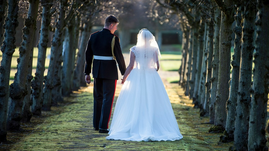 bride wlakes with groom down tree lined avanue