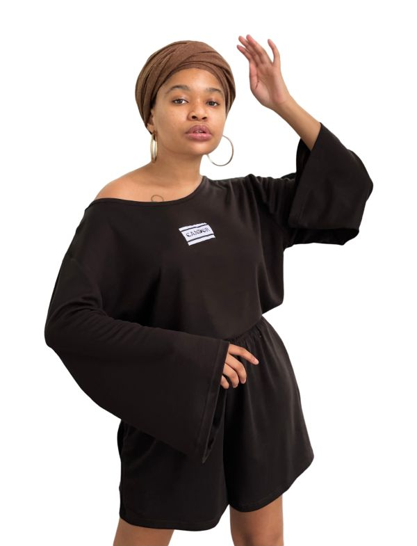 Feminine model in a brown headwrap with one arm raised to the side of her head and the other raised to the hip showcasing the bell sleeve of the Candor Chestnut set. The set is a dark chestnut brown with a wide neck top with bell sleeves and a matching pair of shorts with an elasticated waist and pockets. The top has the signature Candor logo stitched on the front centre.