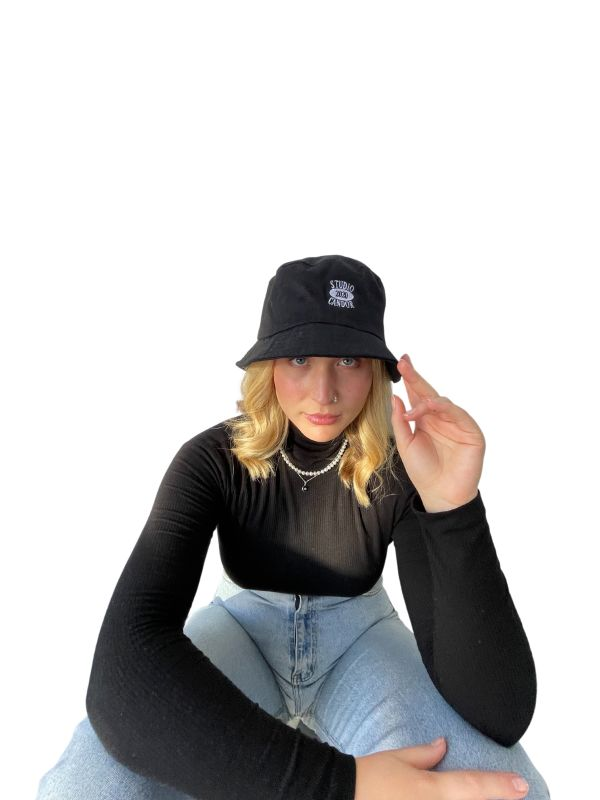 Caucasian feminine model sitting against a plain white background with her legs out of frame and left hand lifted up to her head. Model is wearing vintage-style blue jeans, a black polarneck and a black Candor Bucket Hat with white vintage-style 'Studio Candor 2020' logo embroidered centre front.
