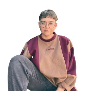 Non-binary caucasian model sitting against a plain white background, wearing vintage black jeans and the Candor Turkish Delight Jersey. The jersey is a vintage-style sweatshirt made up of contrasting vertical panels in a maroon and tan fleece blend fabric. Candor text logo is embroidered centre front of the jersey.