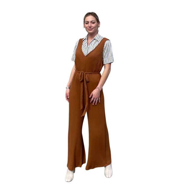 Caucasian feminine model facing forward against a white background. She is wearing the Candor Libra Jumpsuit, with a thrifted striped button up vintage top underneath.