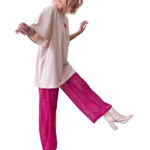 Caucasian feminine model stood mid-step in the Candor Taurus Set, facing away from the camera in front of a whited out backdrop. The Taurus pants is a hot pink zig-zag mesh pants that is see-through with an orange elasticated waistband. It is paired with an oversized Taurus T-shirt so as to provide some modesty if the client so desired.
