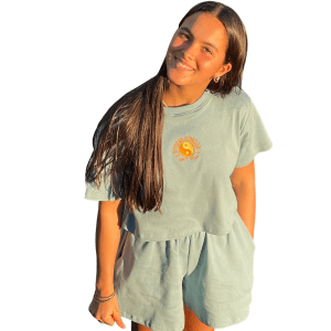 Feminine model in the Candor Topaz set. Smiling with hands by her side and looking up into camera. Set is light wash blue with elasticated shorts with pockets. Top has orange and yellow yin-yang embroidery on the front centre.