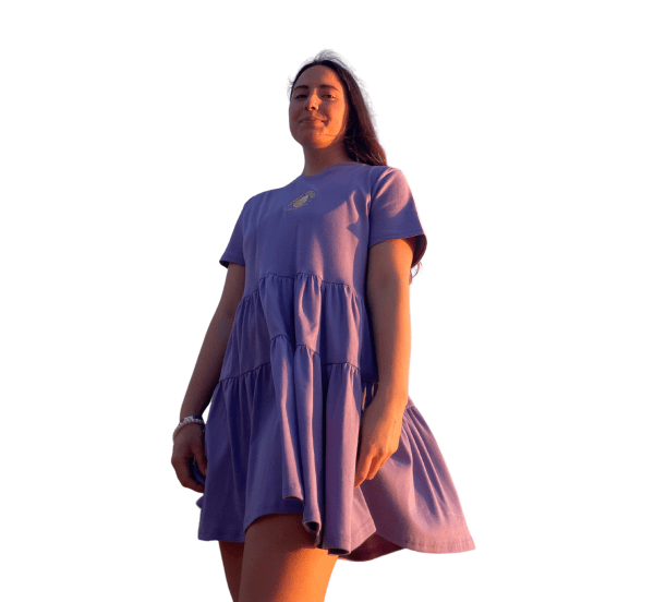 """Feminine model in front of a white backdrop, wearing the Candor Aries dress. The dress is a lavender short-sleeve with a three-tiered gaged skirt. It has yellow and white yin-yang embroidery in the center front with the words """"studio candor since 2020"""" embroidered around the symbol."""