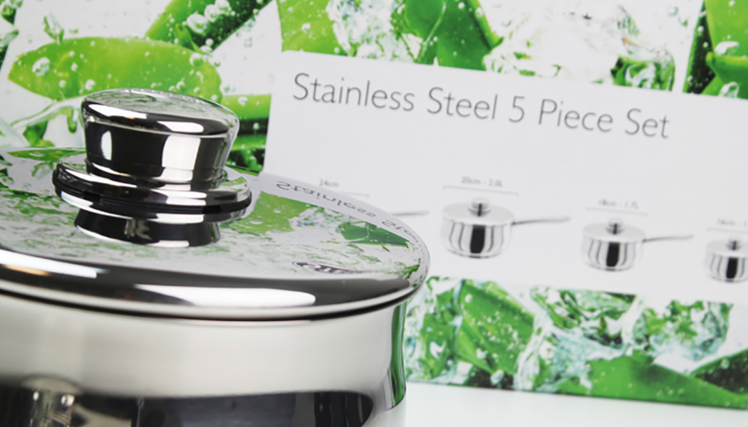 Stellar cookware stainless steel saucepan with lid in front of packaging for five piece set
