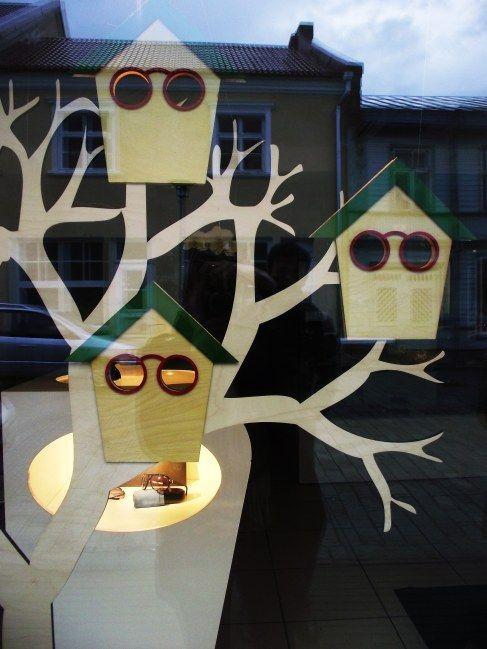 Escaparate de óptica con silueta de árbol y casitas de pájaro, diseño súper original