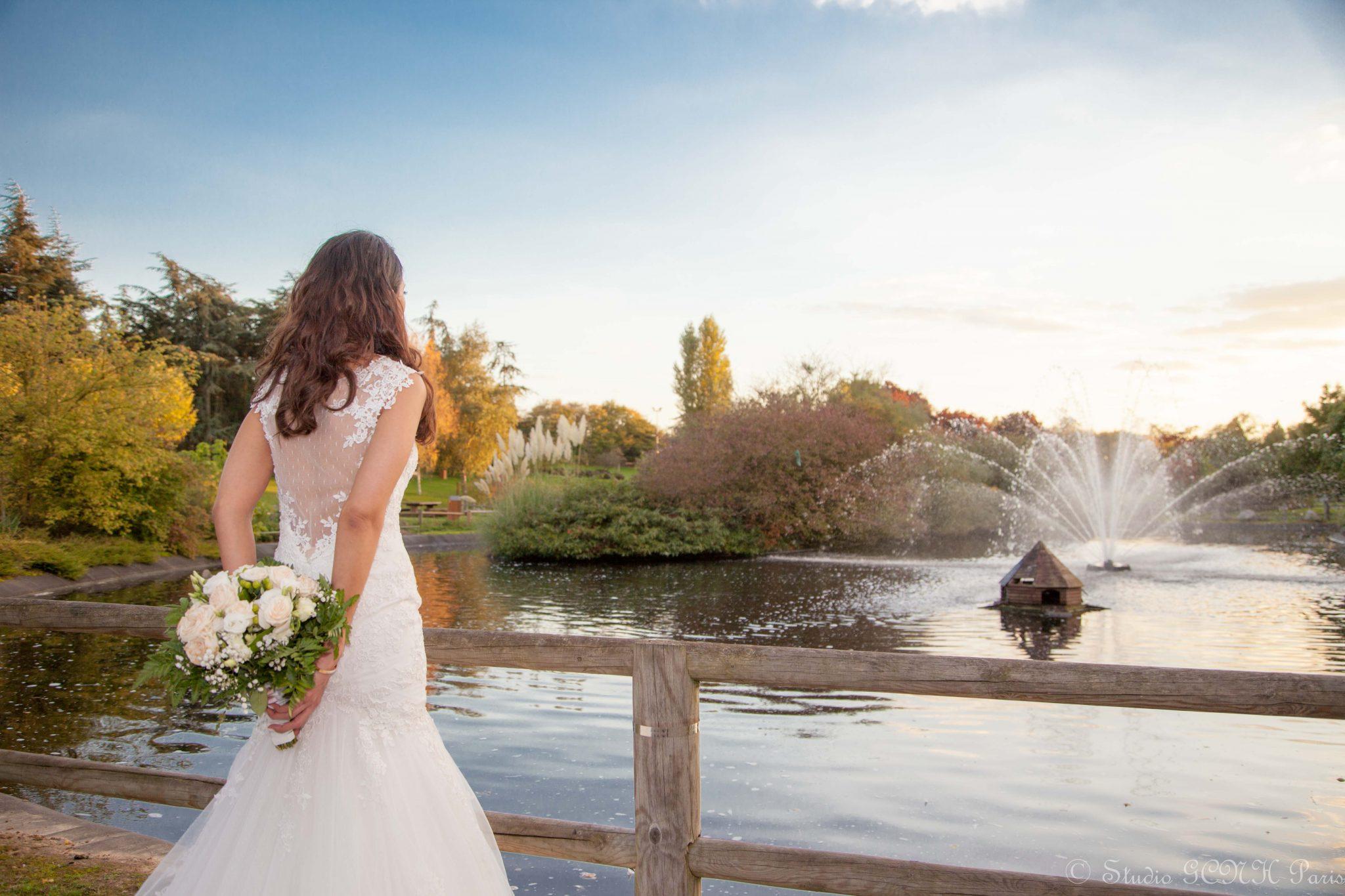 photographe de mariage mariée dans parc avec bouquet ciel bleu