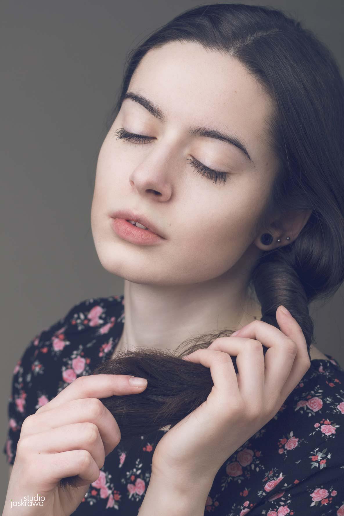 kobieta plecie warkocz z ciemnych włosów