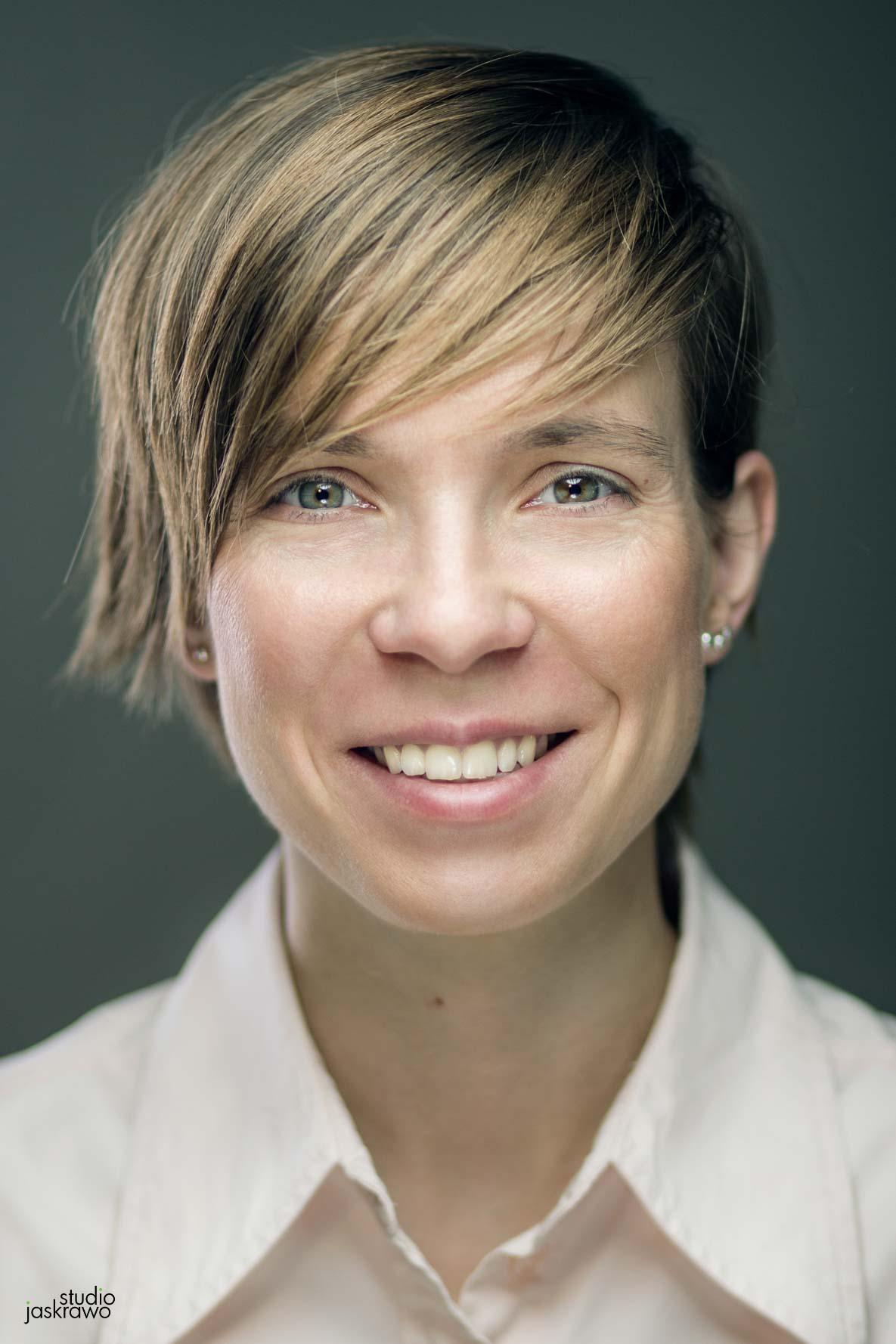 twarz uśmiechniętej kobiety z krótkimi włosami