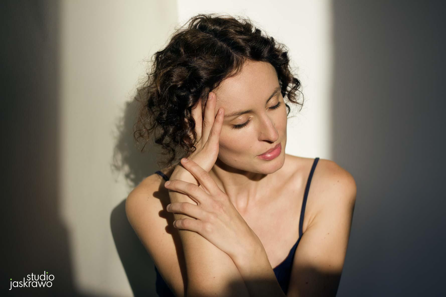 brunetka z kręconymi włosami trzyma ręce przy twarzy