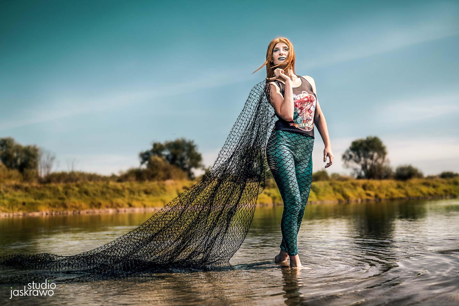 syrenka morska stoi w rzece i trzyma sieć rybacką