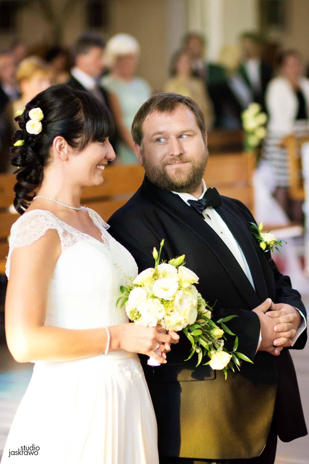 pan młody patrzy w oczy pani młodej podczas ich ślubu w kościele