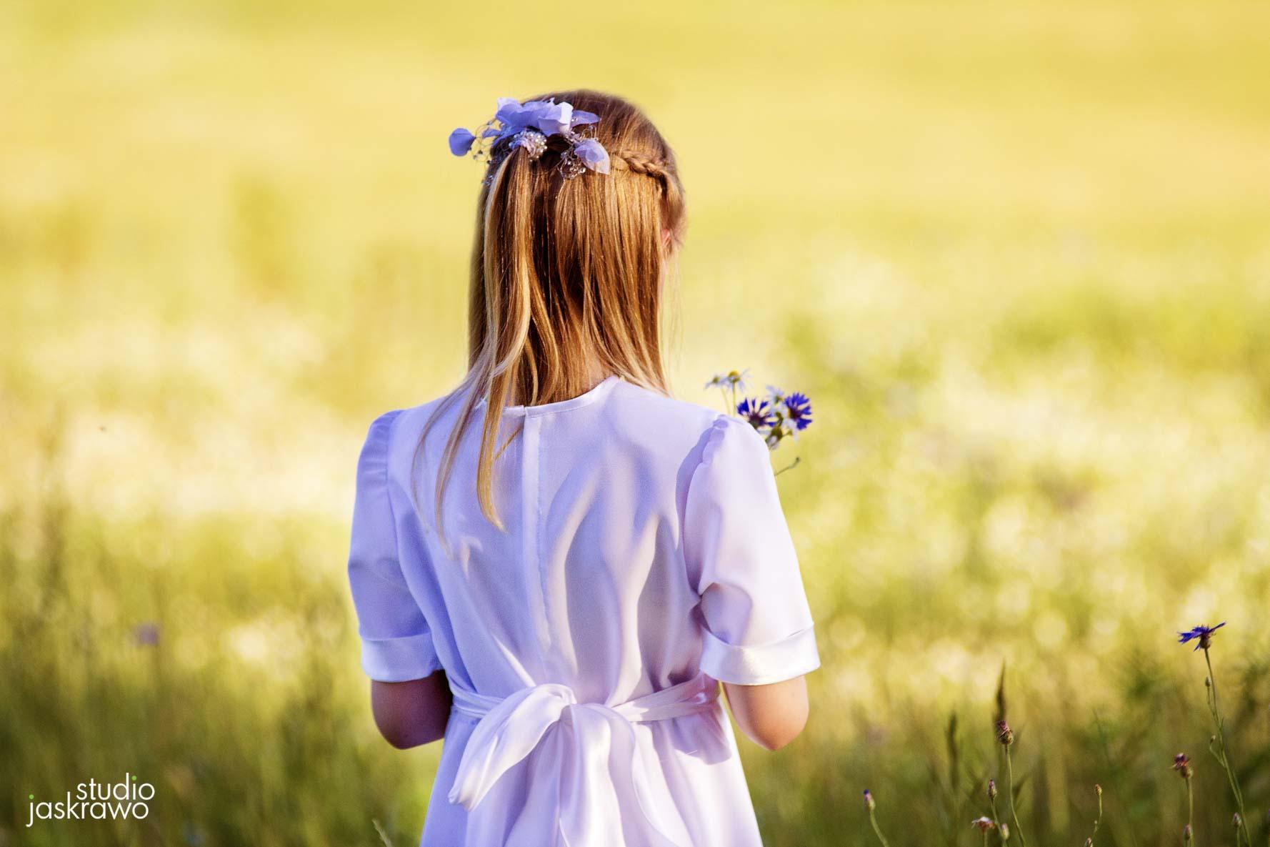 odwrócona dziewczynka w sukience komunijnej na zielonej łące