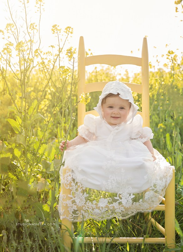 baby in baptism gown in field of yellow flowers in Currituck, NC