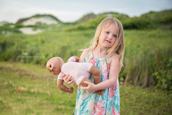 little girl holding baby doll by dunes of Coquina Beach, nags head NC