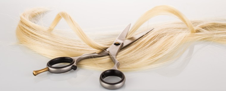 Hairdressing Scissors with a strand blond hair on a light background close-up