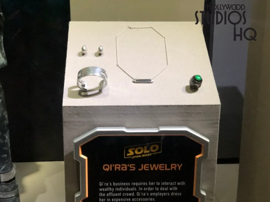 Guests visiting Disney's Star Wars Launch Bay gallery can see Han Solo's authentic Corellia costume in intricate detail. The clothing Han Solo wore during his street thief days is modeled by a full size figure. Guests can view Han Solo with clothing and accessories representative of his association with the White Worms gang. In a nearby full glass display case, viewers will also marvel at the Corellia costume worn by the 18 year old Qi'ra. This character in the Solo: Star Wars motion picture stands in full array. Her show case also displays unique accessories and props from the upcoming film, such as a Range Trooper helmet, originally worn by specialized solders whose role was to defend Imperial interests in frontier settlements. Visitors can see both life size costumes on display in this front gallery. Disney's Hollywood Studios. Photo by John Capos.