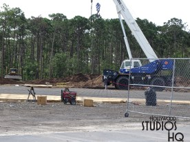 Crews have recently erected a new metal structure in a wooded area across from the rear of the existing guest parking lot. This may eventually be serving as vehicle entrance ticket booths along the new entrance roadway. This structure's visible metal roofing has a design similar to the roof projections of the Park's existing guest main entrance. Meanwhile construction workers continue making headway on the vehicle overpass supports at the Osceola Parkway and Victory Lane intersection. Disney's Hollywood Studios. Photo by John Capos