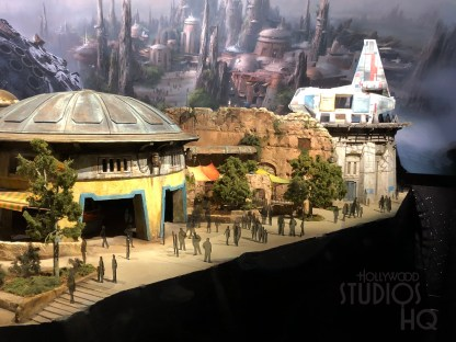 A new partial scale model of the future Star Wars: Galaxy's Edge was unveiled this week inside Walt Disney Presents. Replacing the former Toy Story Land model display, this large scale outlay under a clear dome details some of the outposts as well as a replica of the famous Millennium Falcon and a Resistance Intersystem Transport. Fans are also able to view a nearby large color TV screen that alternates views of the full scale Planet of Batuu, complete with a First Order AT-AT Walker. Disney's Hollywood Studios. Photo by John Capos