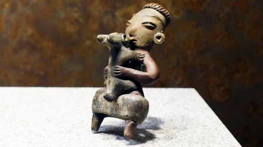 Tlatilco figurine of a woman kissing a dog