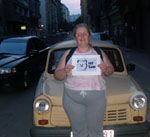 Lynn with Hi Sam banner in front of yellow car