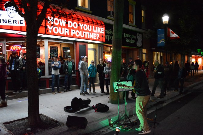 A busker plays music outside Smoke's Poutinerie on York Street in the early evening as people wandering the street draw near to listen.