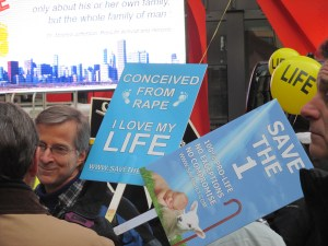 man holding save the one protest signs at Chicago March for Life