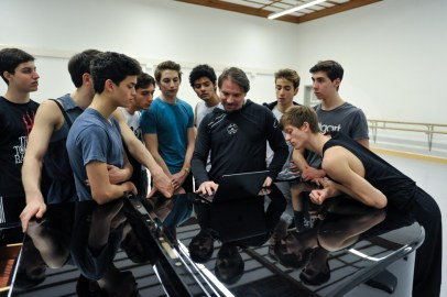 Ballettmeister Rolando D'Alesio schaut mit den Tänzern eine Videoaufzeichnung an