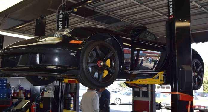2017 Porsche L.A. Literature, Toy and Memorabilia Meet Weekend: Black Porsche Carrera GT, left front, on rack at Callas Rennsport during the 2017 Porsche Lit Week. Credit: StuttgartDNA