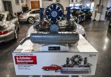 Franzis' Porsche Flat-Six Engine Scale Model Kit: Six-cylinder engine kit on kit packaging with 911s in bg. Credit Flat Six Fanatics