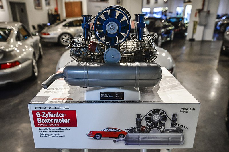 Franzis' Porsche Flat-Six Engine Scale Model Kit: Six-cylinder engine kit on kit packaging with 911s in bg. Credit Flat Six Fanatics