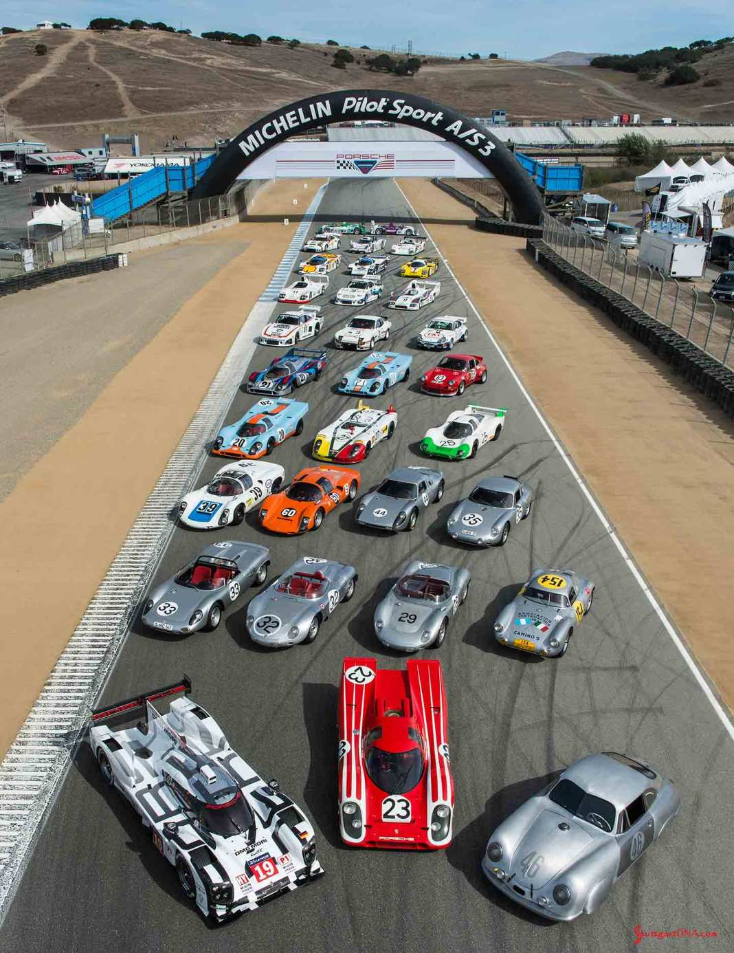 Porsche announces 2018 Rennsport Reunion VI: Shown here on the lower Laguna Seca straightaway between Turns 3 and 4 is the 2015 Porsche Rennsport Reunion V family portrait showing a diverse sampling of Porsche race cars. The grouping spans from the No. 46 356 SL Gmund Coupe to the present-day 919 Hybrid, both Le Mans winners in their respective heydays. Credit: Porsche AG