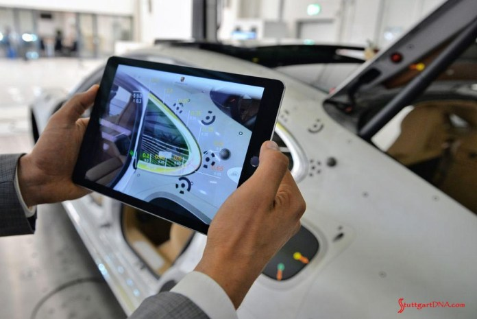 Porsche Inno-Space quality-control program: An example of the Inno-Space tecnology; a tablet is held over a B-pillar window to detect any flaws. Credit: Porsche AG