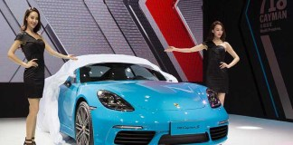 April 2018 Porsche USA sales: This photo depicts Porsche at Auto China World premiere in Beijing of the 718 Cayman mid-engine sport coupé, flanked by two lovely Chinese models (twins?).