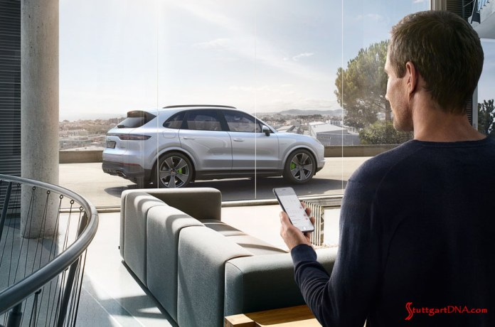 "What are ""Porsche Drive"" and ""Porsche Host""?: Pictured here is a man checking an app on his smartphone, with silver Cayenne in b.g. outside his office building's glass wall. Credit: Porsche AG"