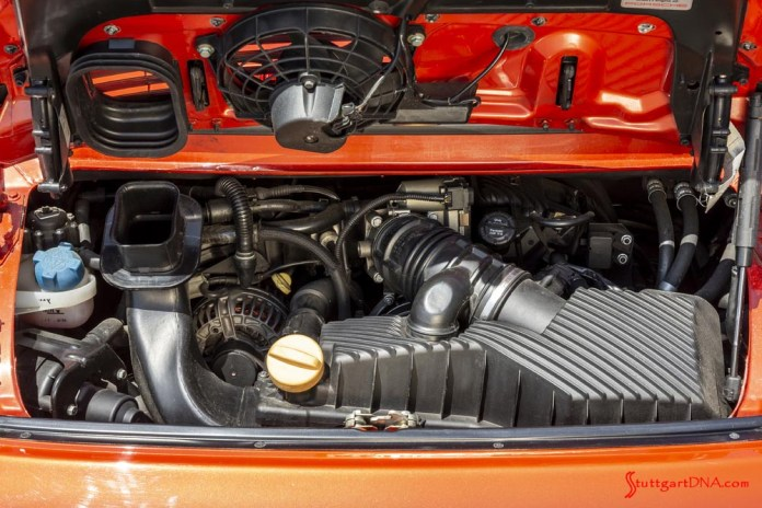 996-gen Porsche 911 Buyer Guide: Pictured here is an example of the first 911-production 1998 996 3.4 L water-cooled engine, direct angle, in the engine bay of an orange-bodied 996-gen Porsche 911. Credit: Porsche AG