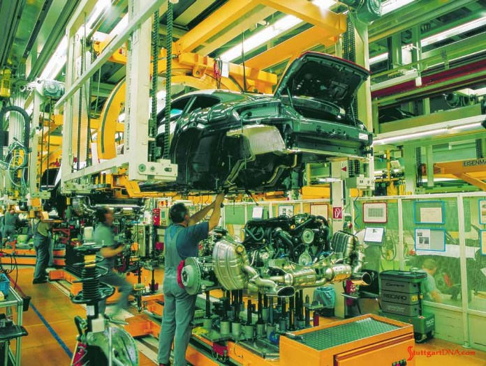 """996-gen Porsche 911 Buyer Guide: Pictured here are """"Hans Jr."""" and """"Franz Jr."""" conducting the marriage of the engine to the chassis and body of a 996-gen Porsche 911, ca. 1998. Credit: Porsche AG"""
