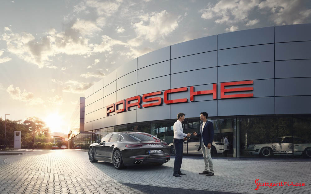 2019 Premier Porsche Dealers list announced: Pictured here is a Porsche dealership's facade at sunset, with the archetypical bold PORSCHE signage lit up in Guards Red. Credit: Porsche AG