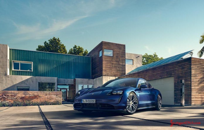 Porsche Taycan first electric sports car world premiere: Depicted here is a blue Taycan next to a charging station in the driveway of a modern home . Credit: Porsche AG