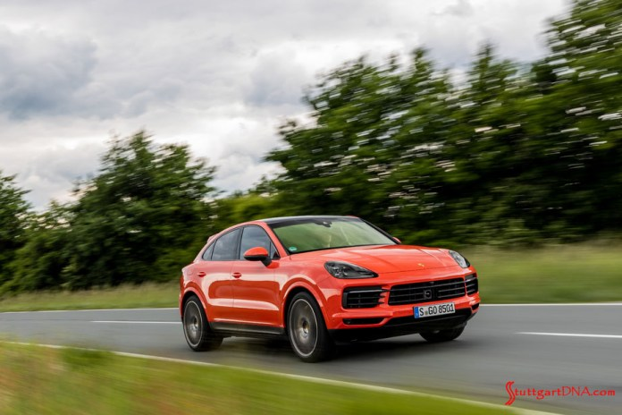 November 2019 Porsche USA sales: This is a photograph of a lava-orange Cayenne coupe, right-front, at speed on a deserted road, with tall green bushes and a cloud-filled sky in b.g. Credit: Porsche AG