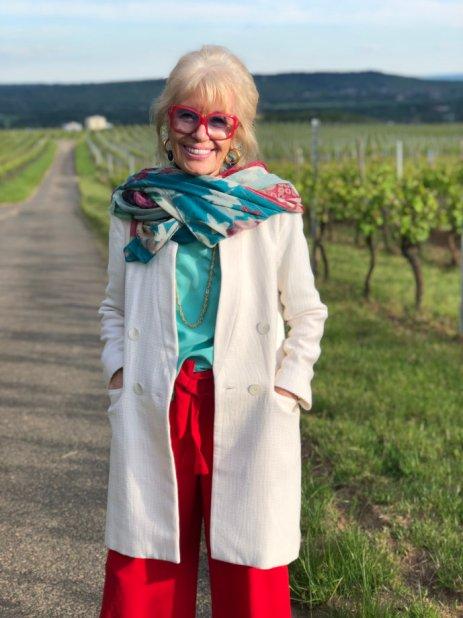 Sommerliche Mode Inspiration: Ein leichter, beiger Mantel, rote Hosen und ein türkises Oberteil