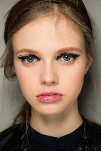 Experiment a doll-like make-up, with a strong black brush stroke on the eyes and soft pink gloss on the lips. (Fendi, FW 2015)