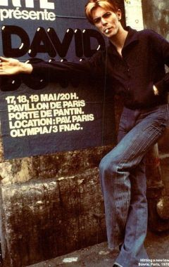 David Bowie in front of a poster of his concert in Paris, 1976