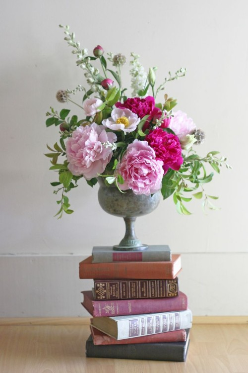 Floral Arrangement of Pink Peonies In Concrete Urn On a Stack of Vintage Books