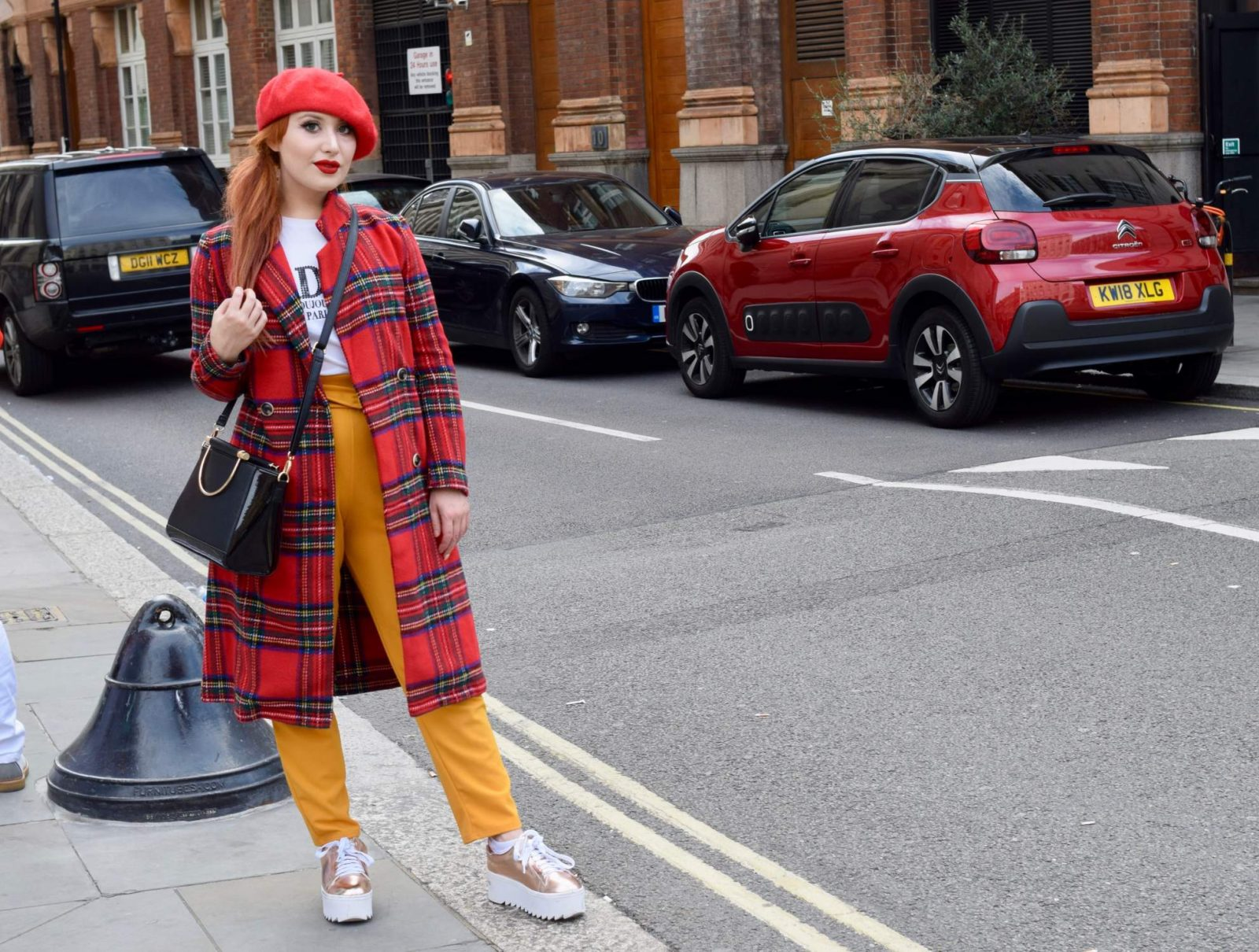 Blogger Twenty-Something City wears tartan coat, red beret and mustard yellow trousers at LFW