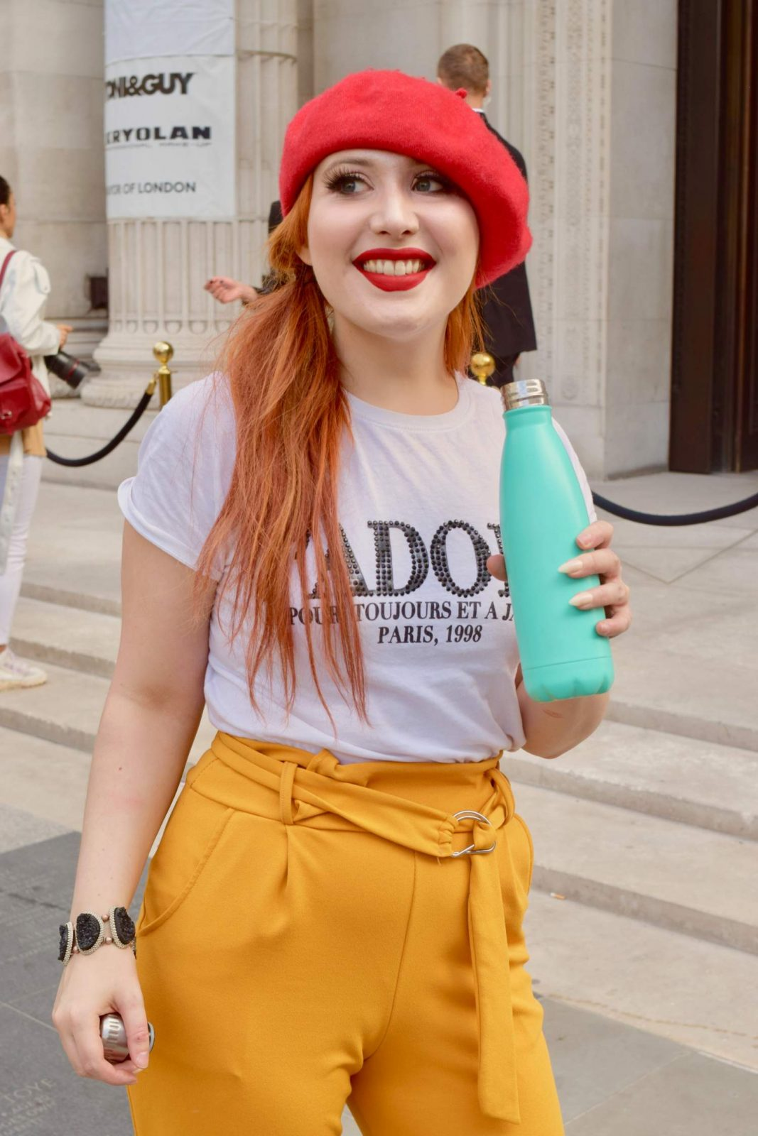 Blogger Twenty-Something City wears red beret and mustard yellow trousers with Turtle Can water bottle LFW