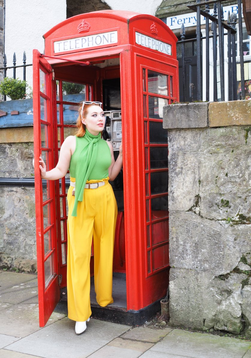 Scottish fashion stylist and blogger Styled by Alice wears a lime green top and sunshine yellow trousers in a red phone box for a colourful outfit