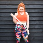 Alice wears colourful gym leggings from BAM and an orange sports bra